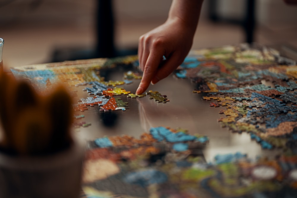 person holding jigsaw puzzle piece