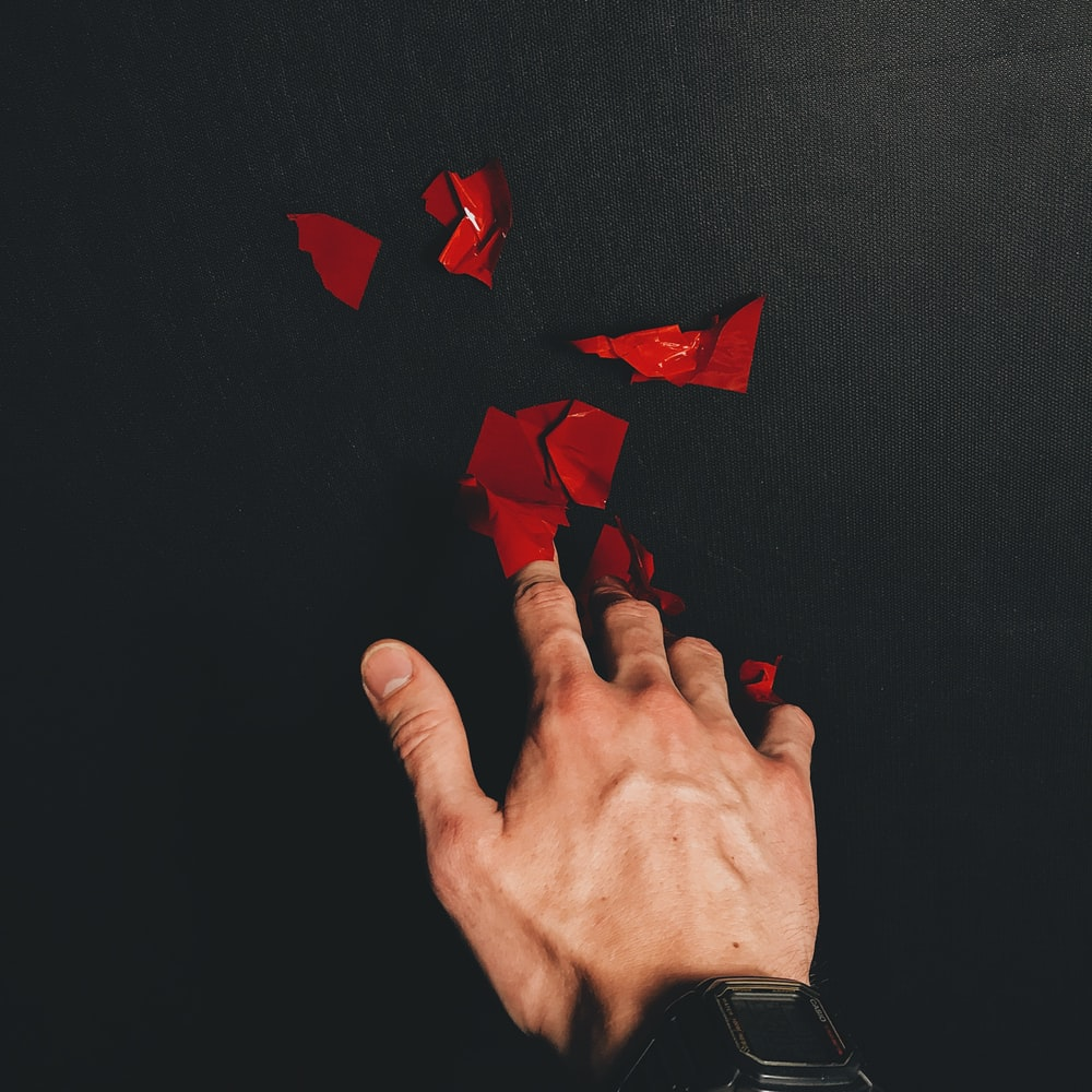 red paper heart on persons hand