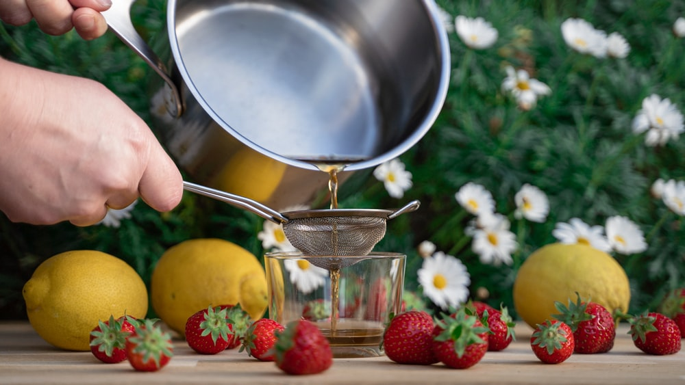 person pouring red strawberries on stainless steel bowl