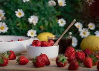strawberries and yellow flowers in white ceramic bowl