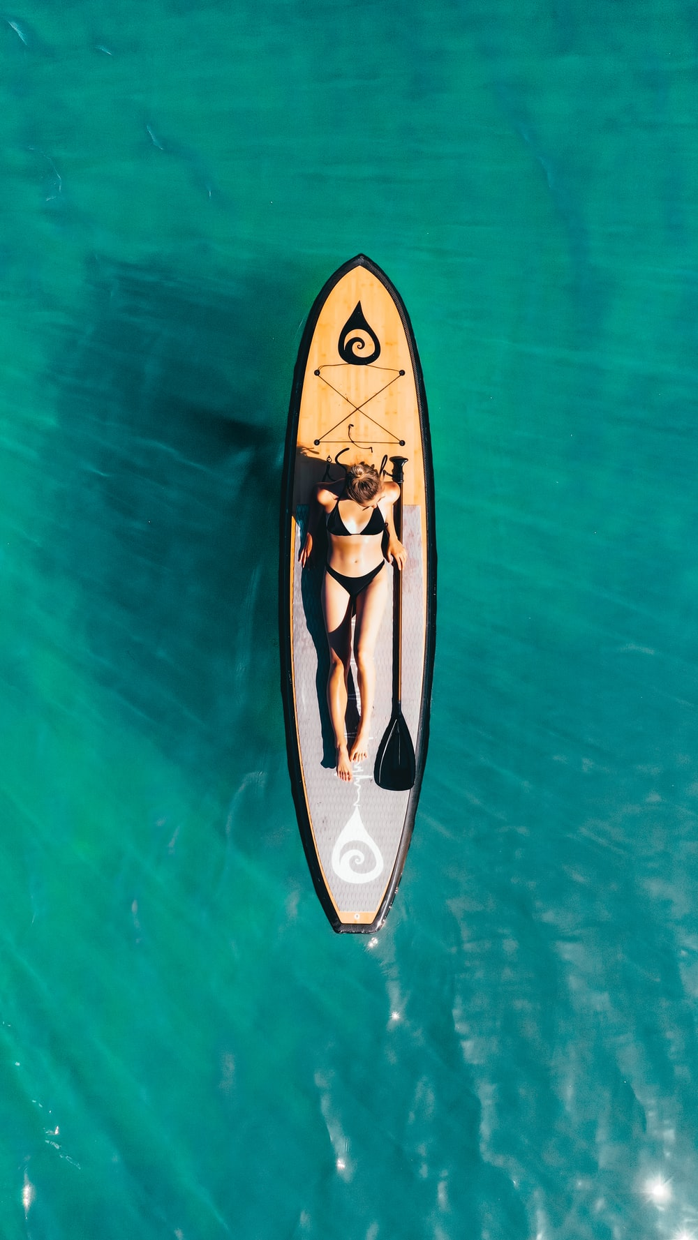 white and black surfboard on body of water