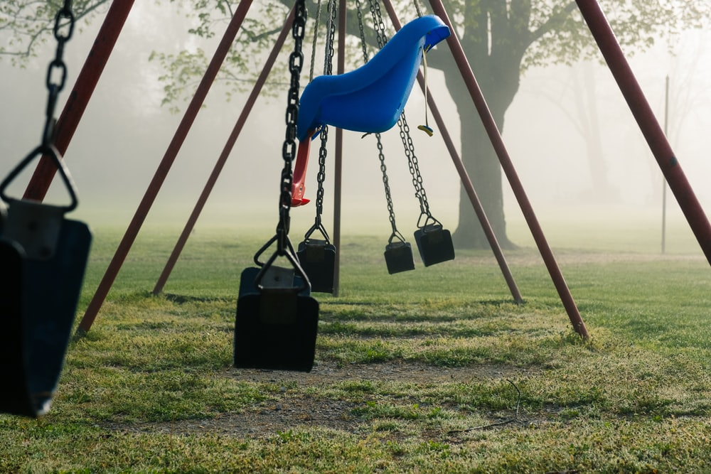 blue swing on green grass field during daytime