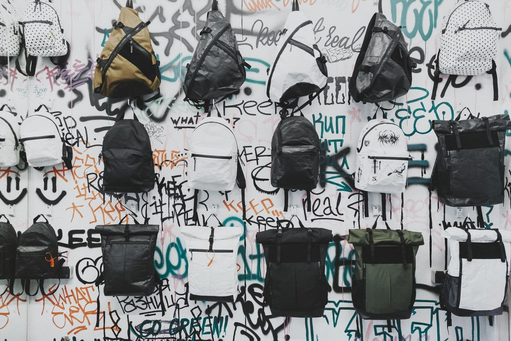 black and brown backpacks on wall
