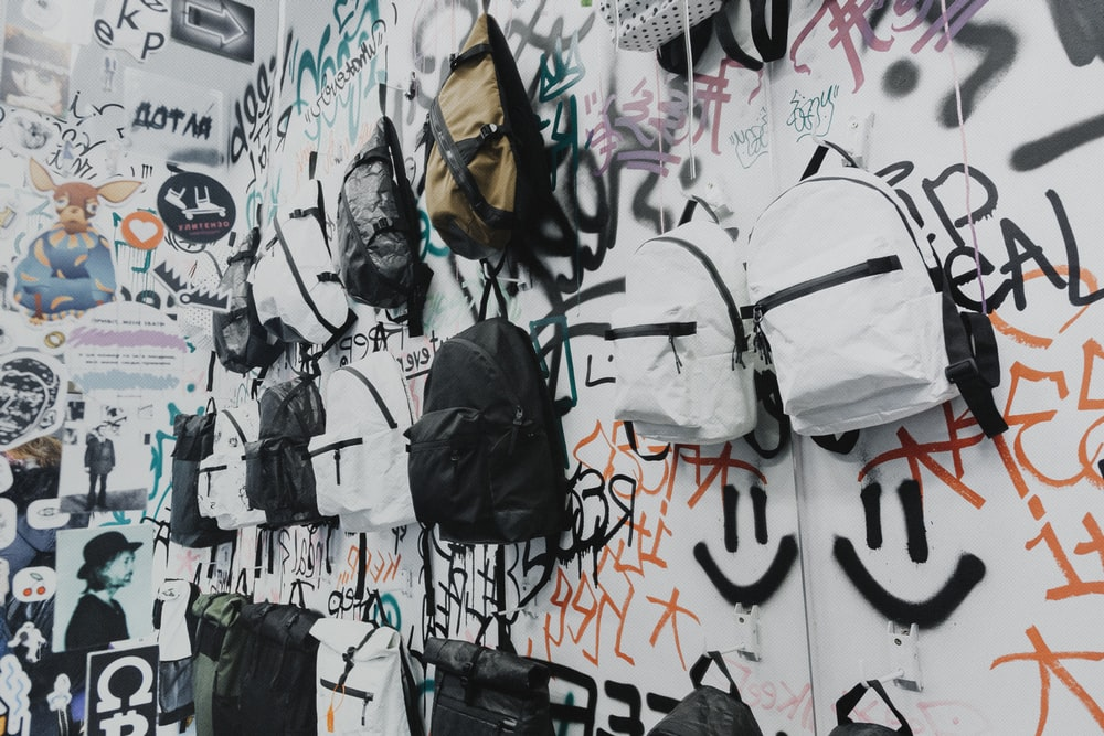 white and black backpack hanged on wall
