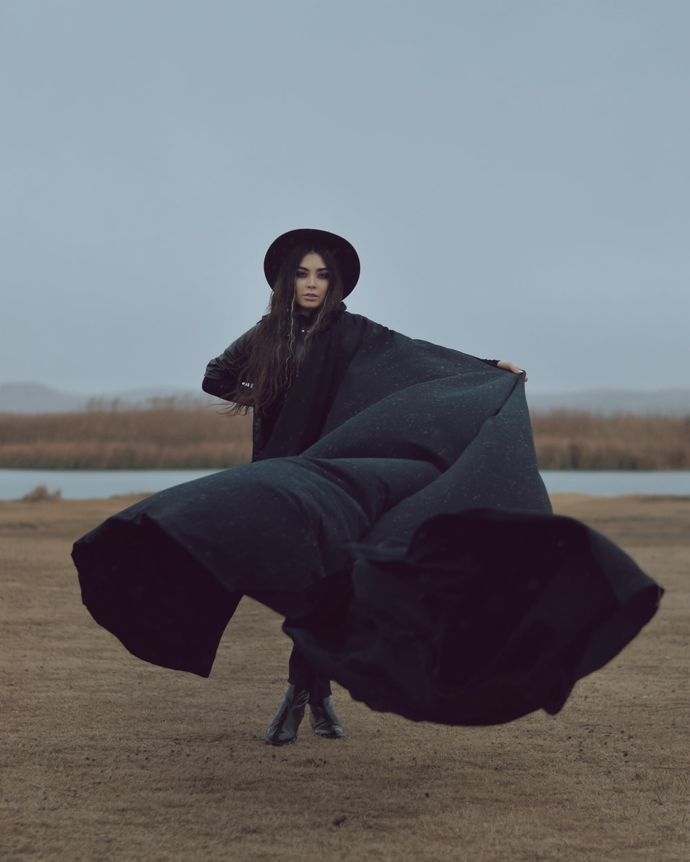 woman in black robe sitting on brown field during daytime