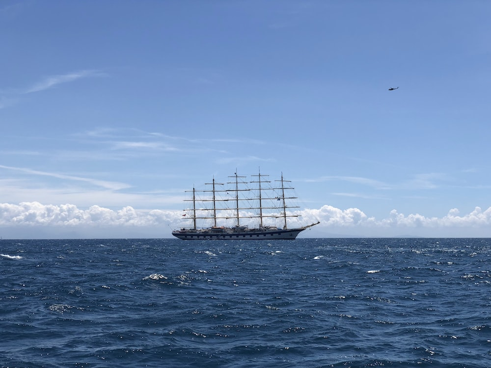 white ship on sea under blue sky during daytime