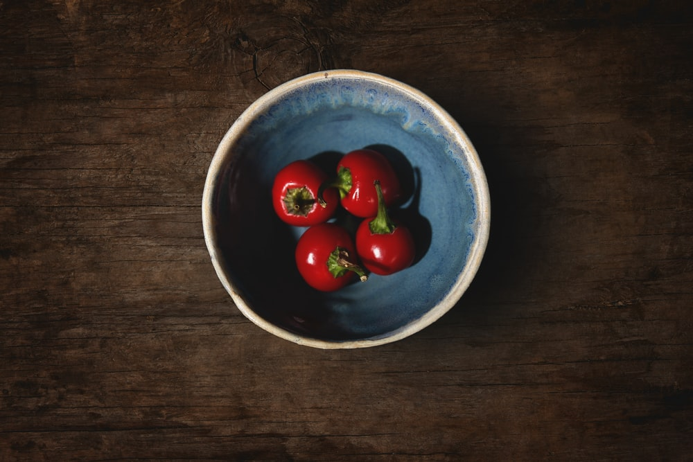 red cherry fruits on blue ceramic bowl