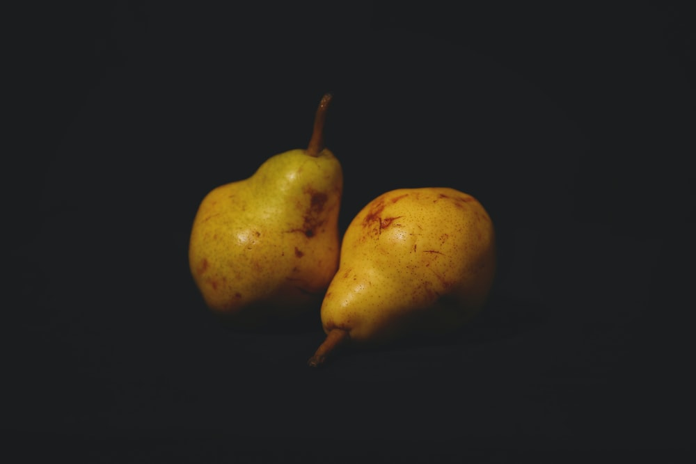 two yellow and green pear fruits