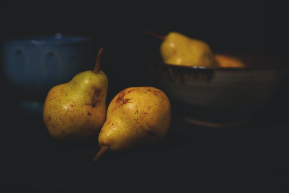 two yellow pear fruits on blue ceramic bowl