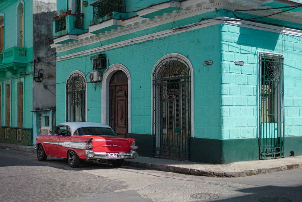 red coupe parked beside blue concrete building during daytime