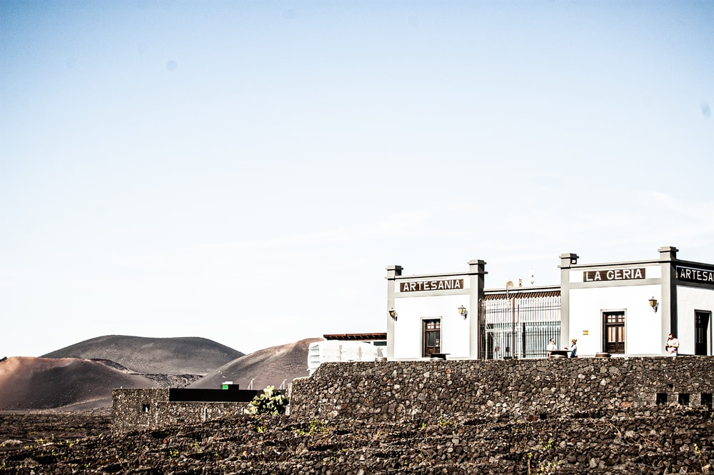 white concrete building on hill