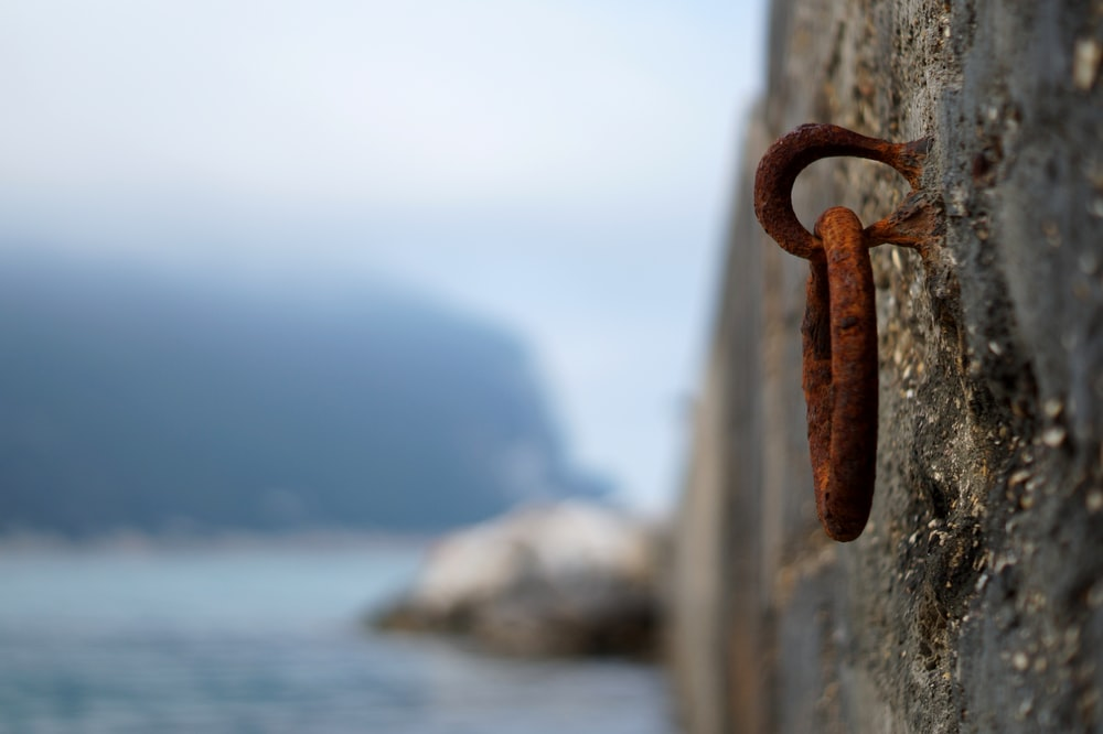 brown metal chain on brown wooden fence near sea during daytime