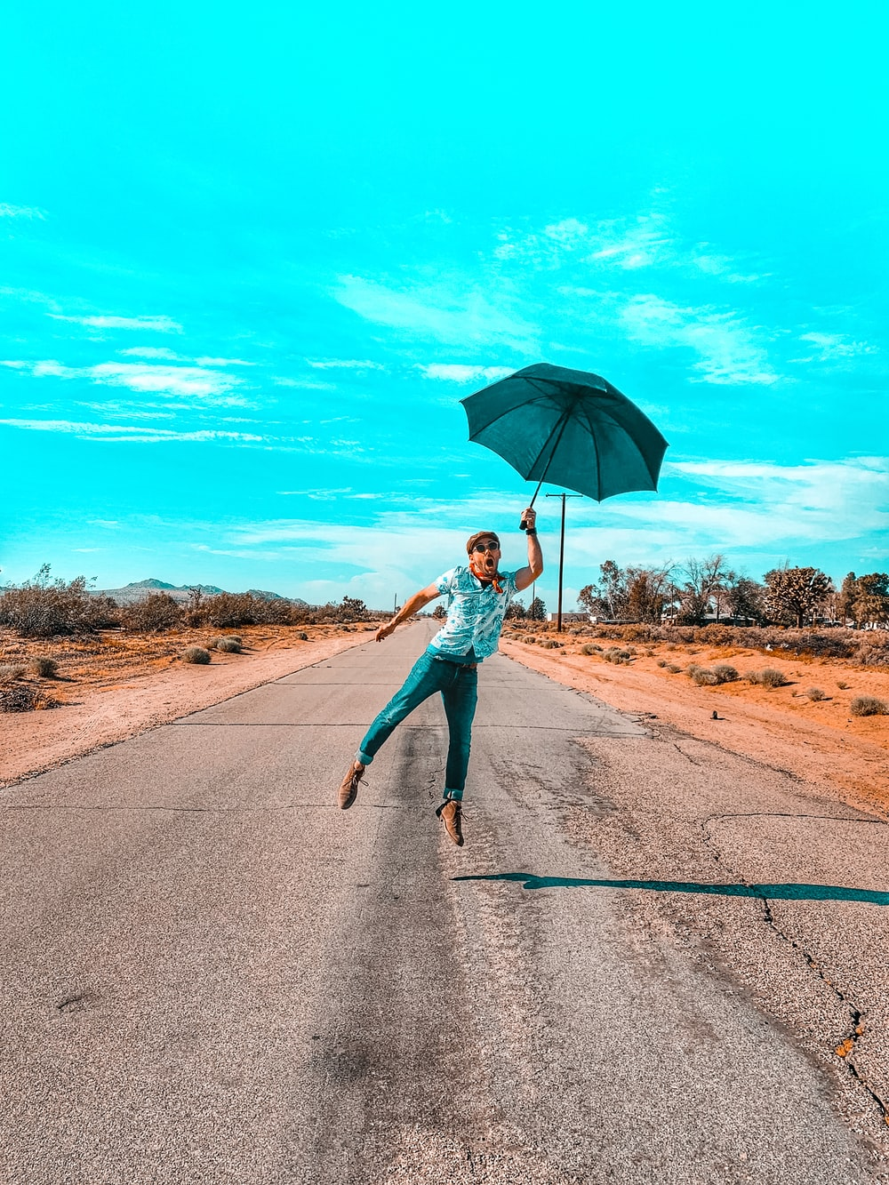 woman in teal long sleeve shirt and blue denim jeans holding umbrella walking on road during