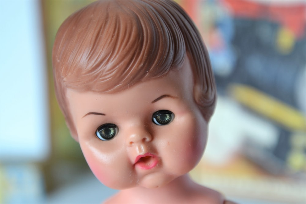 brown haired girl doll in close up photography