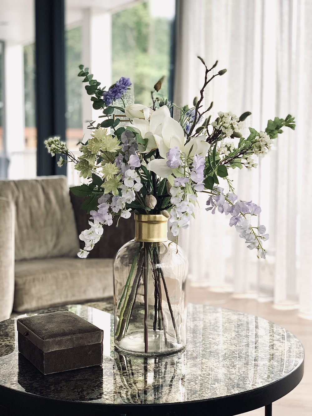 purple flowers in clear glass vase on gray couch