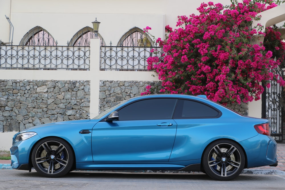 blue coupe parked beside white fence