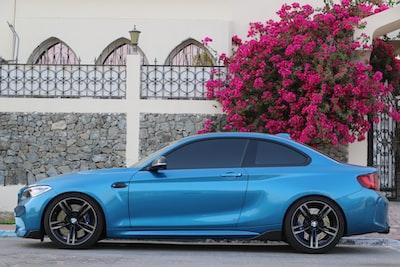 blue coupe parked beside white fence united arab emirates zoom background