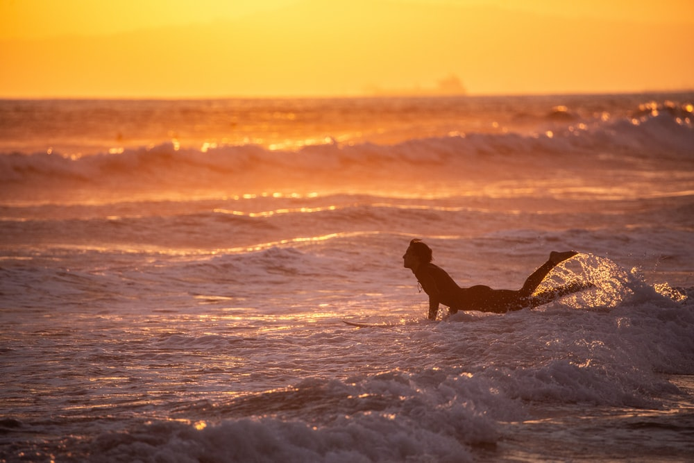 woman sitting on beach shore during sunset