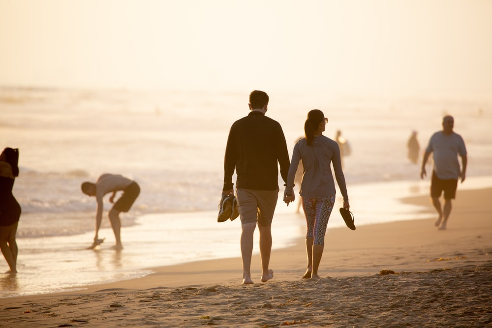 man and woman holding hands while walking on beach during daytime