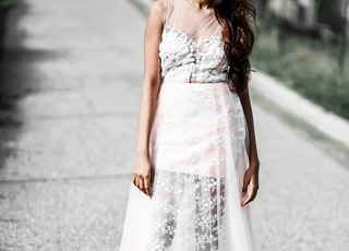 woman in white floral sleeveless dress standing on road during daytime