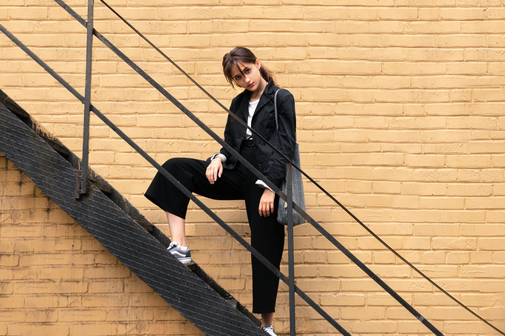 woman in black blazer standing on stairs