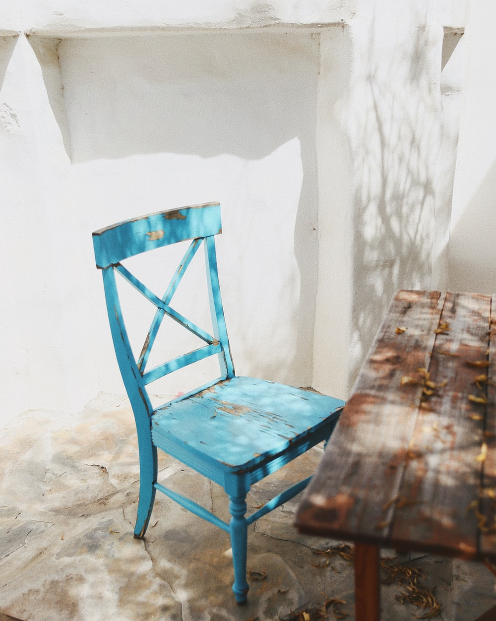 blue wooden chair beside white wall