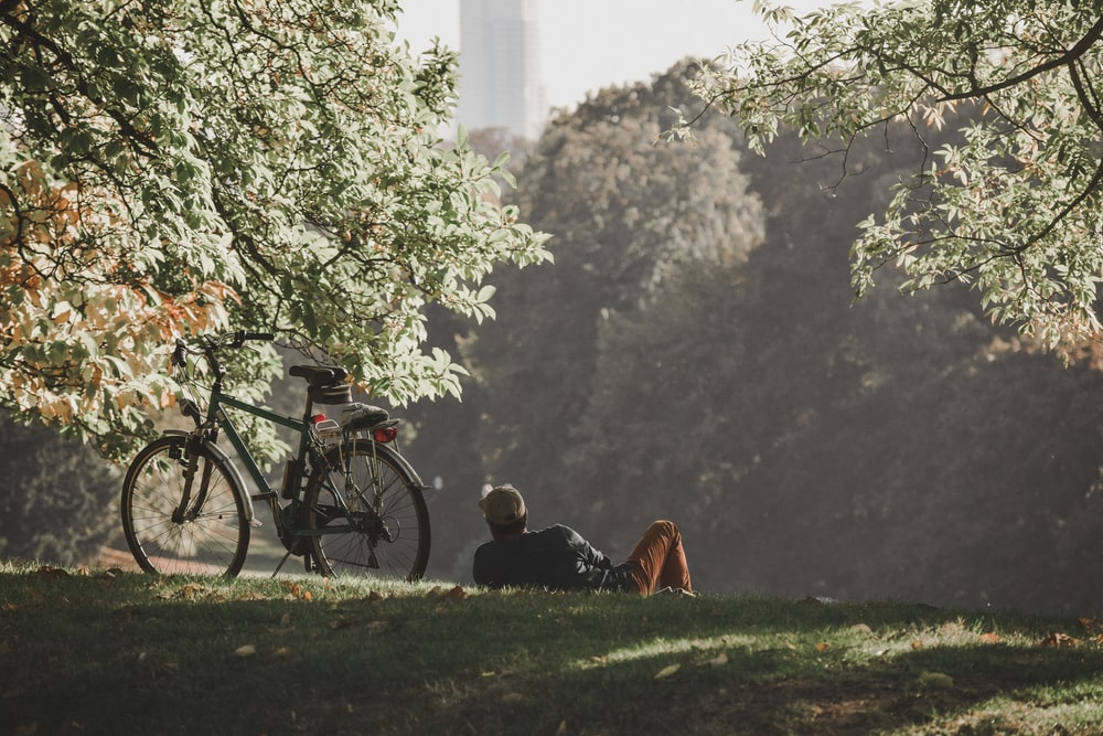 man in black jacket sitting on green grass field near black bicycle during daytime
