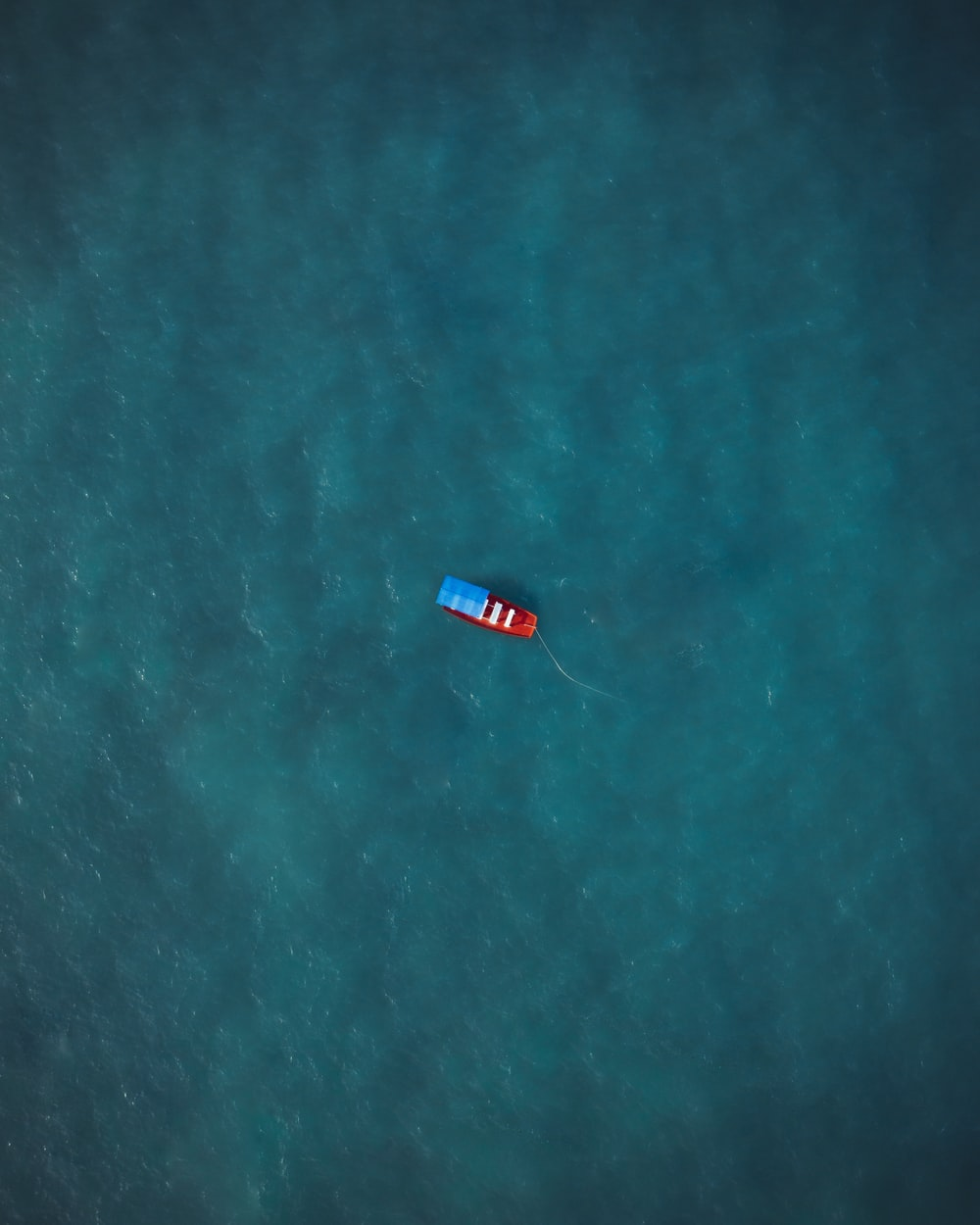 red boat on body of water during daytime