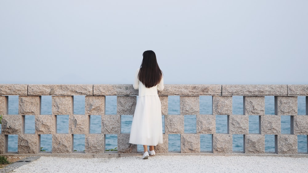 woman in white dress standing on concrete blocks during daytime
