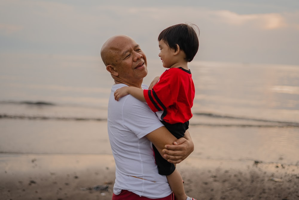 man in white and red polo shirt carrying boy in white and red shirt