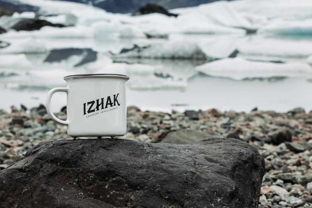 white ceramic mug on rocky shore during daytime