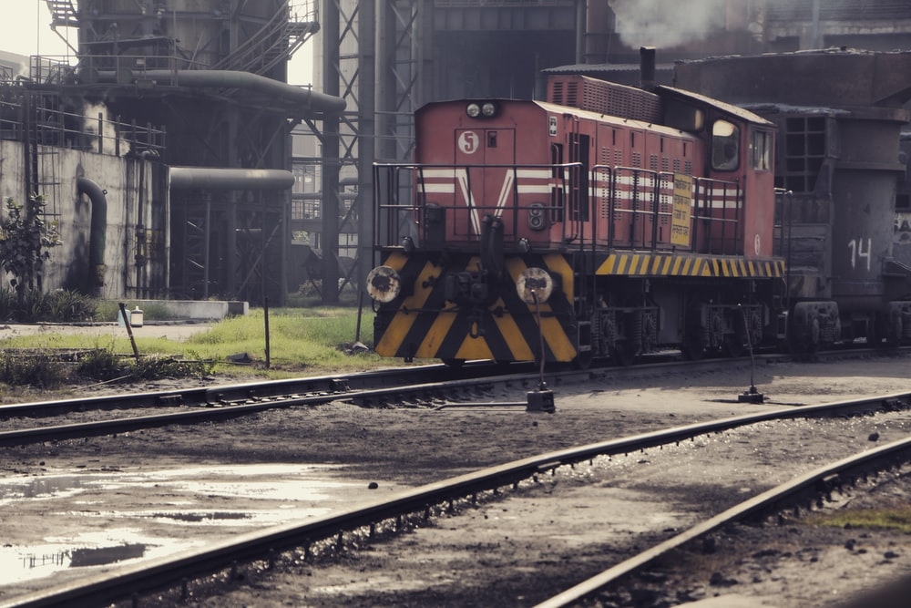 red and yellow train on rail tracks