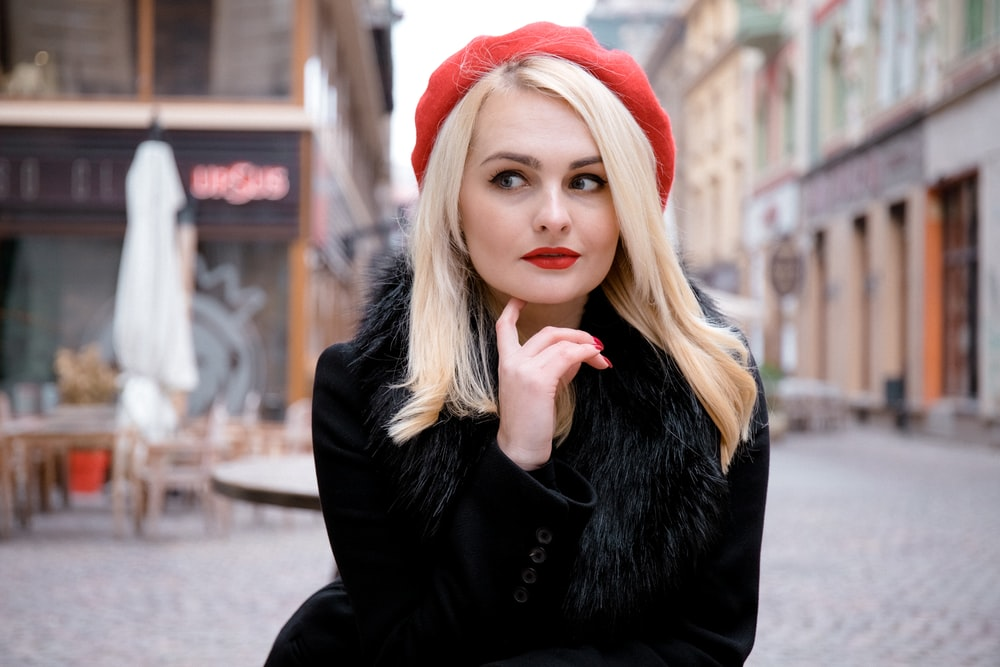 woman in black jacket and red knit cap