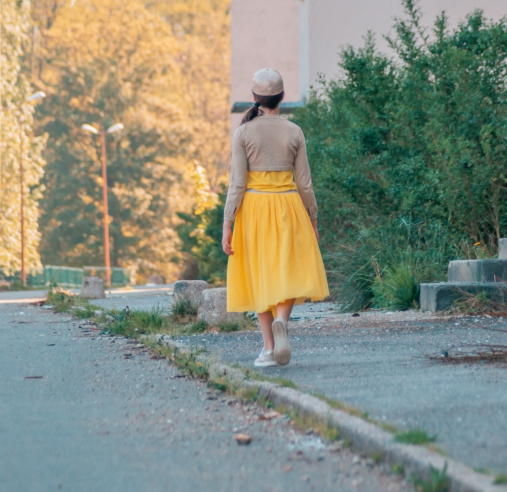 girl in yellow dress walking on gray concrete road during daytime