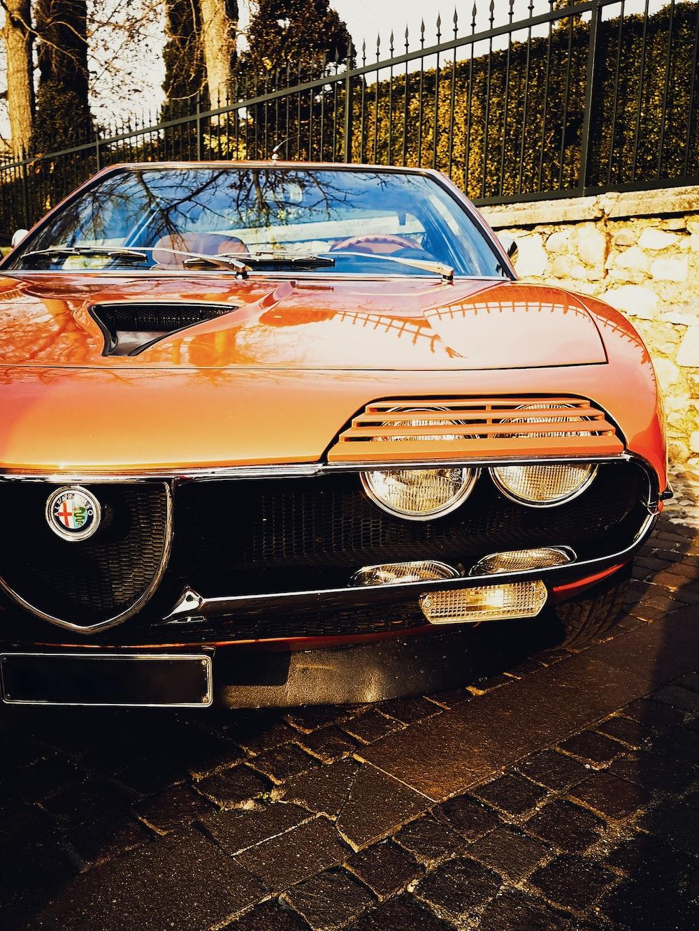 orange classic car parked beside brick wall