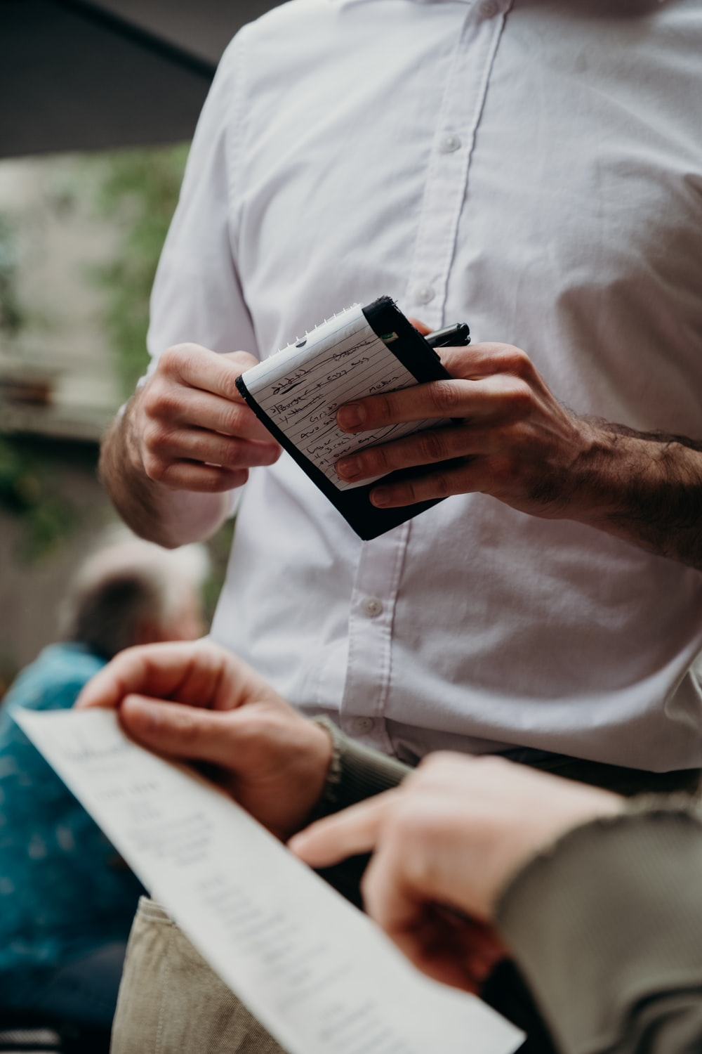 man in white button up shirt holding black and white box
