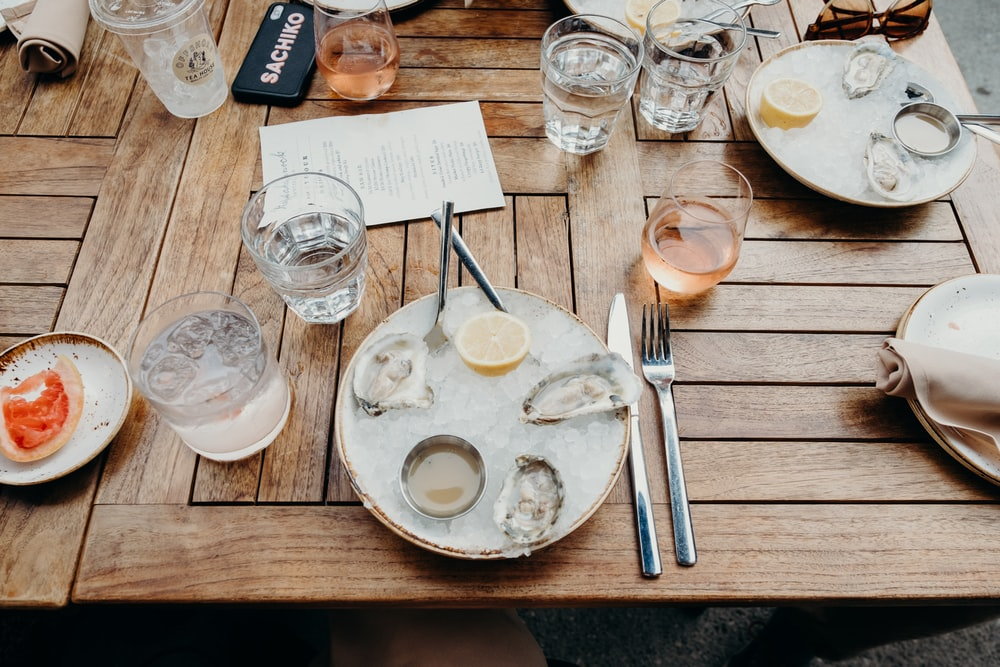 stainless steel spoons on white ceramic plate beside drinking glass on brown wooden table