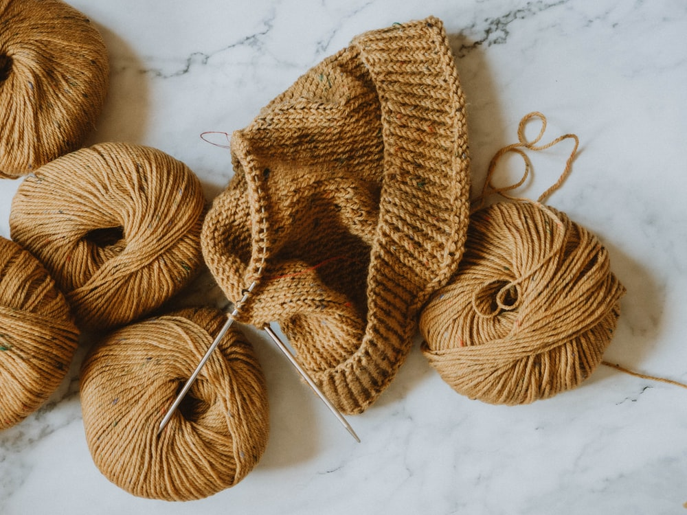 brown knit cap on white textile