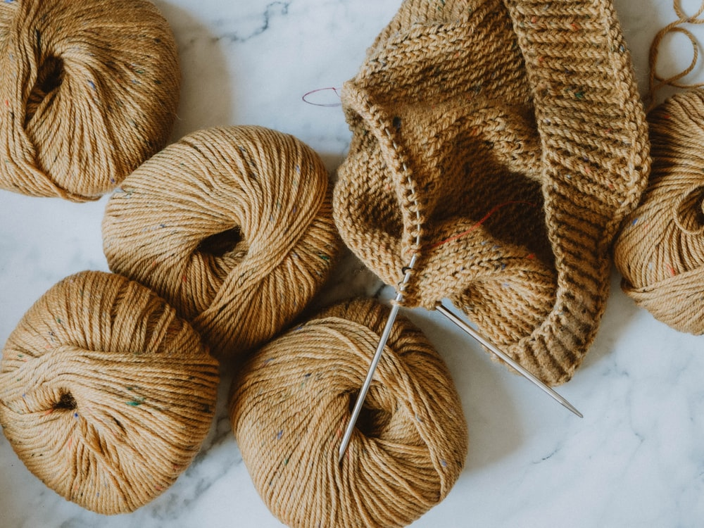 brown yarn on white textile
