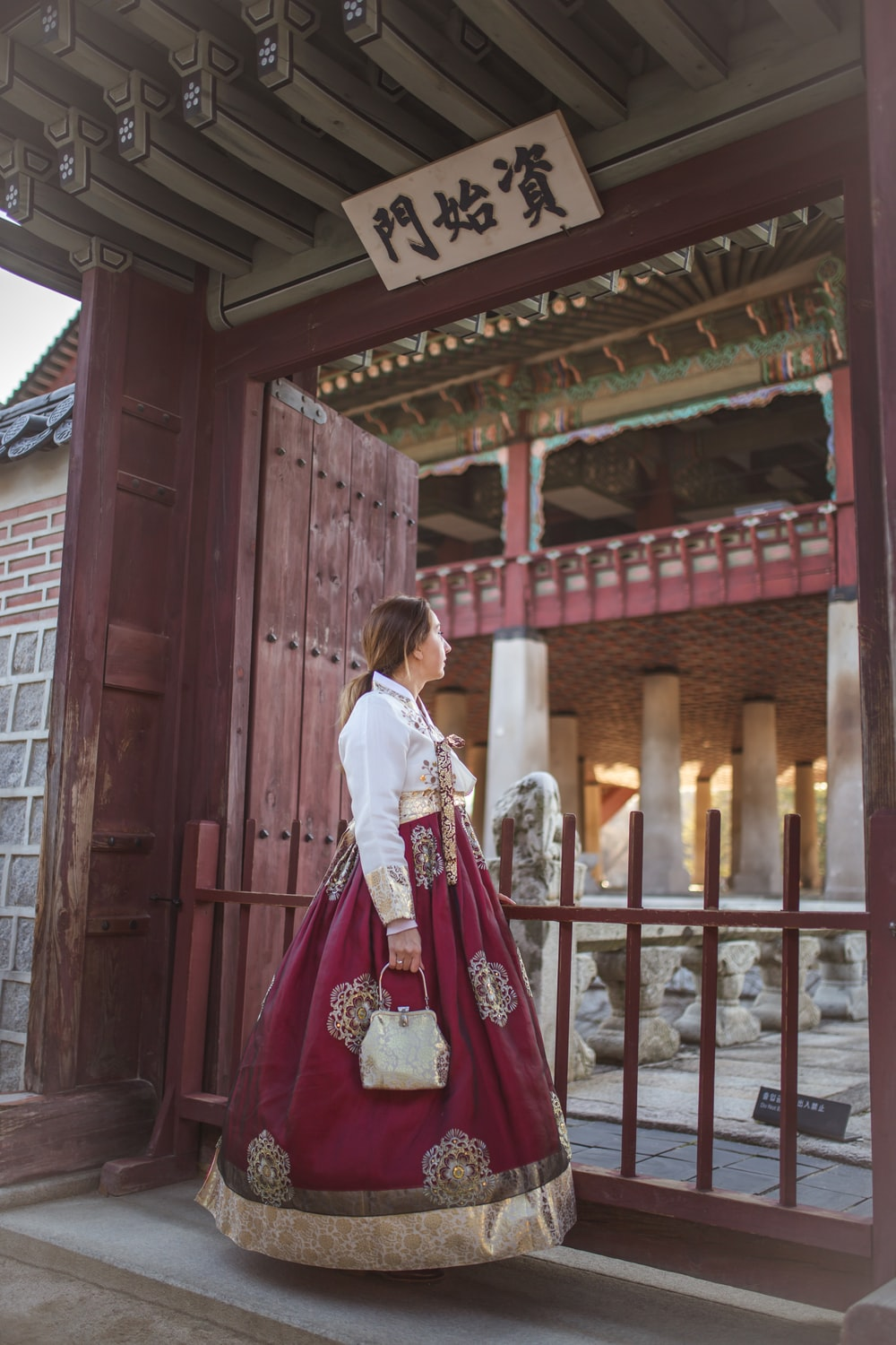 woman in white long sleeve shirt and red skirt standing beside brown wooden door during daytime