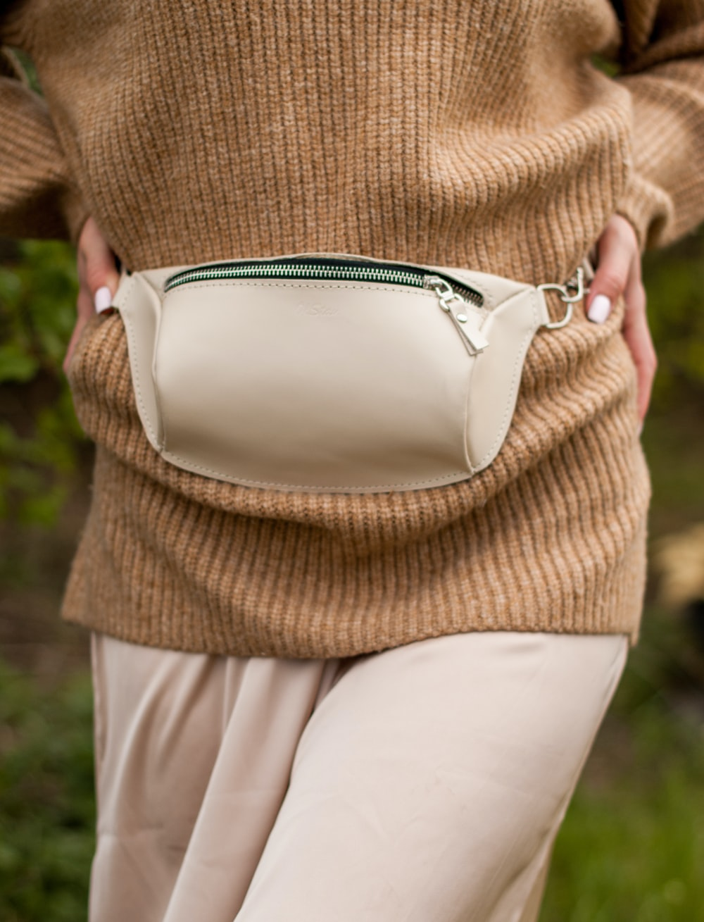 woman in brown knit sweater and white pants