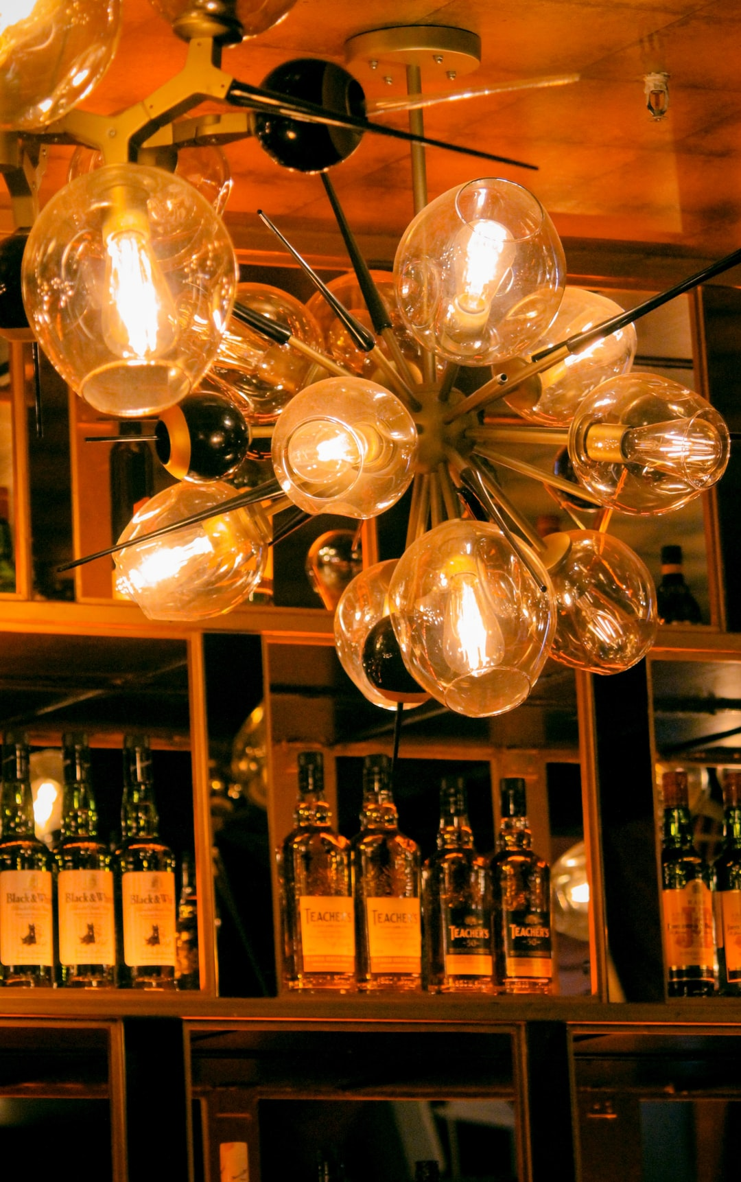 Incandescent ceiling bulbs with wine bottles in background