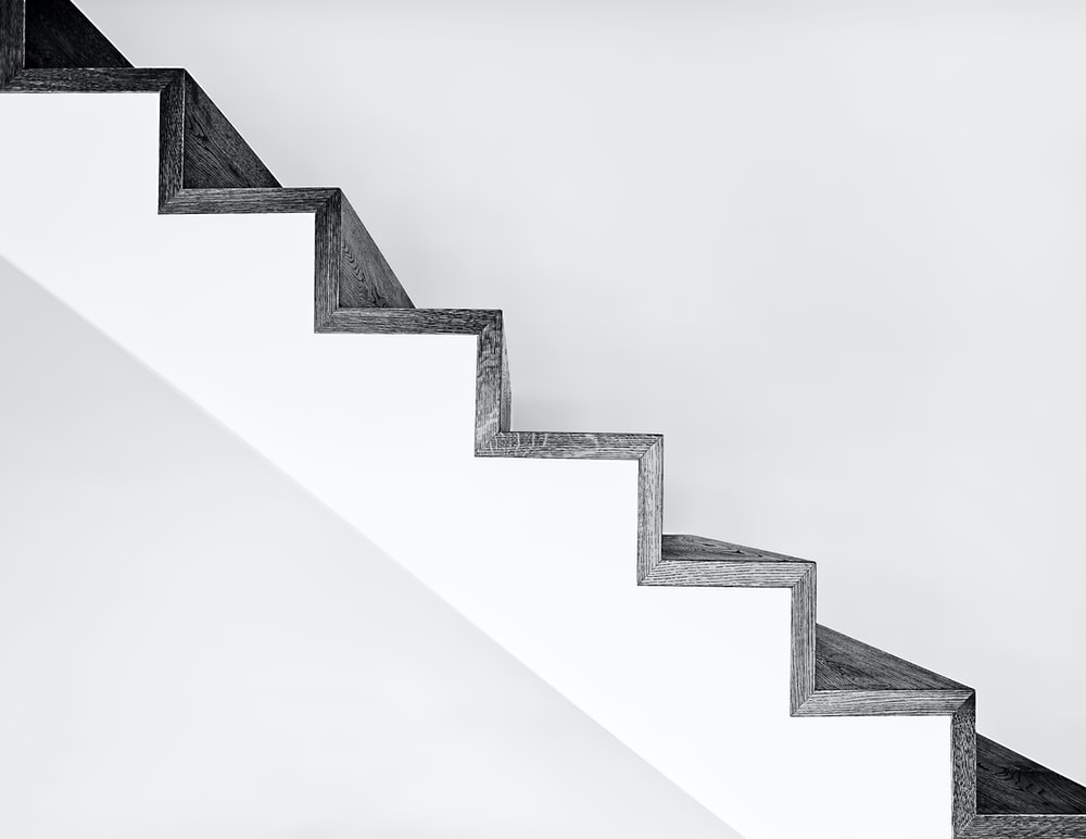 white concrete stairs with black metal railings