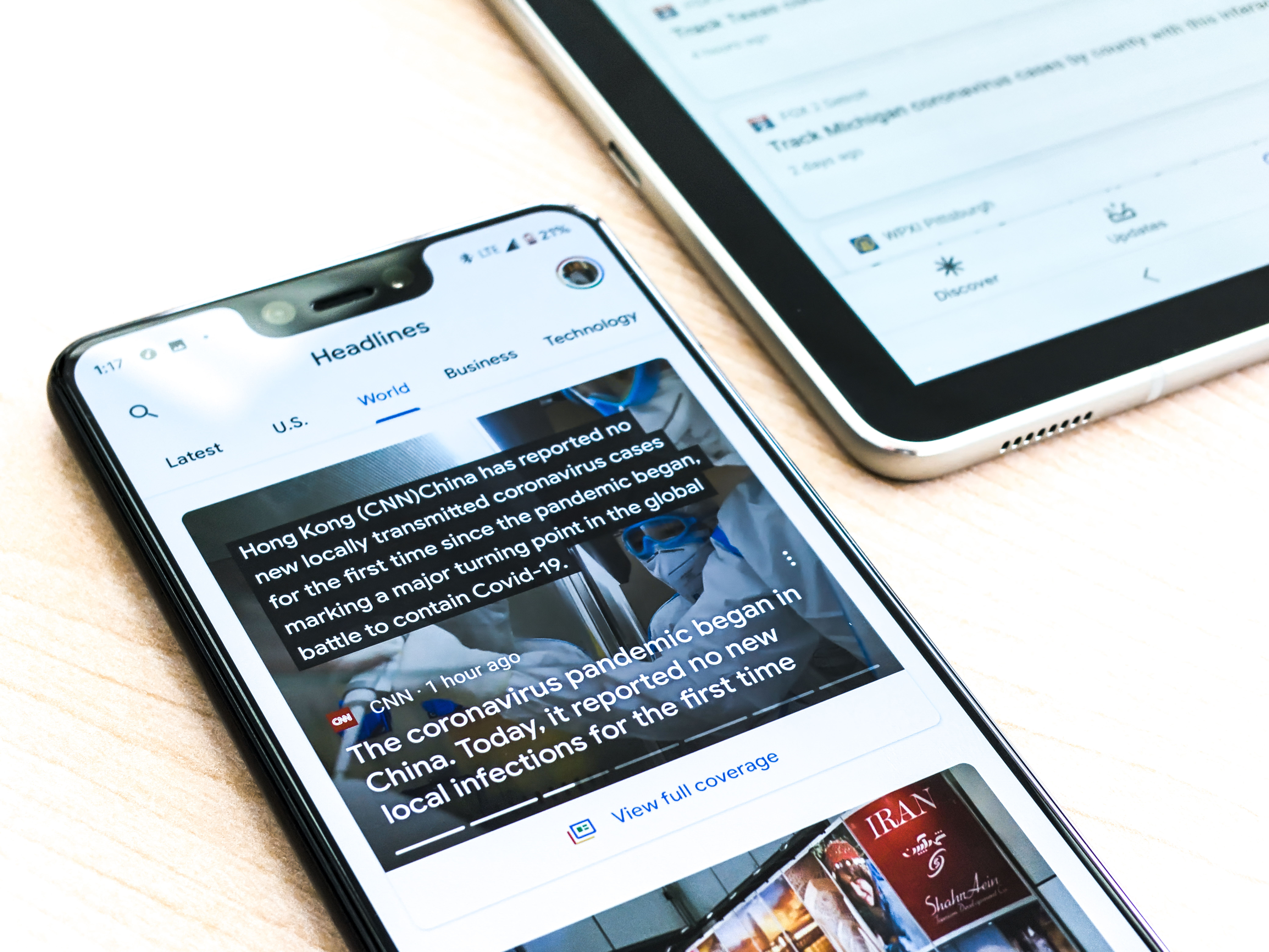 A Google pixel 3XL showing Covid-19 information from the Google News app sits on a wooden table next to a Samsung Galaxy Tablet.