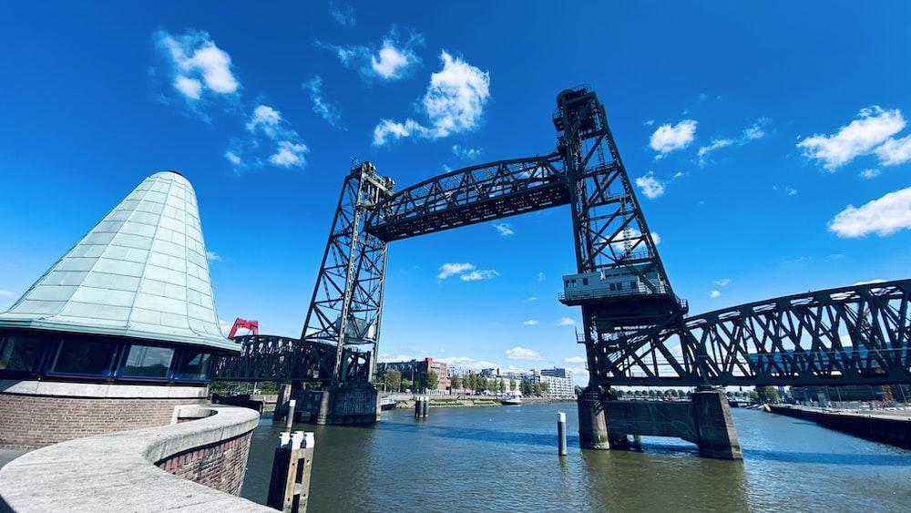 blue metal bridge over body of water during daytime