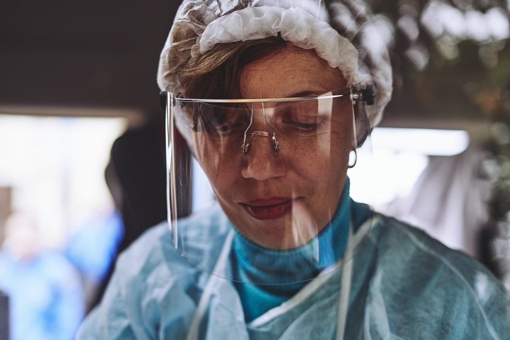 woman in teal scrub shirt wearing white head band