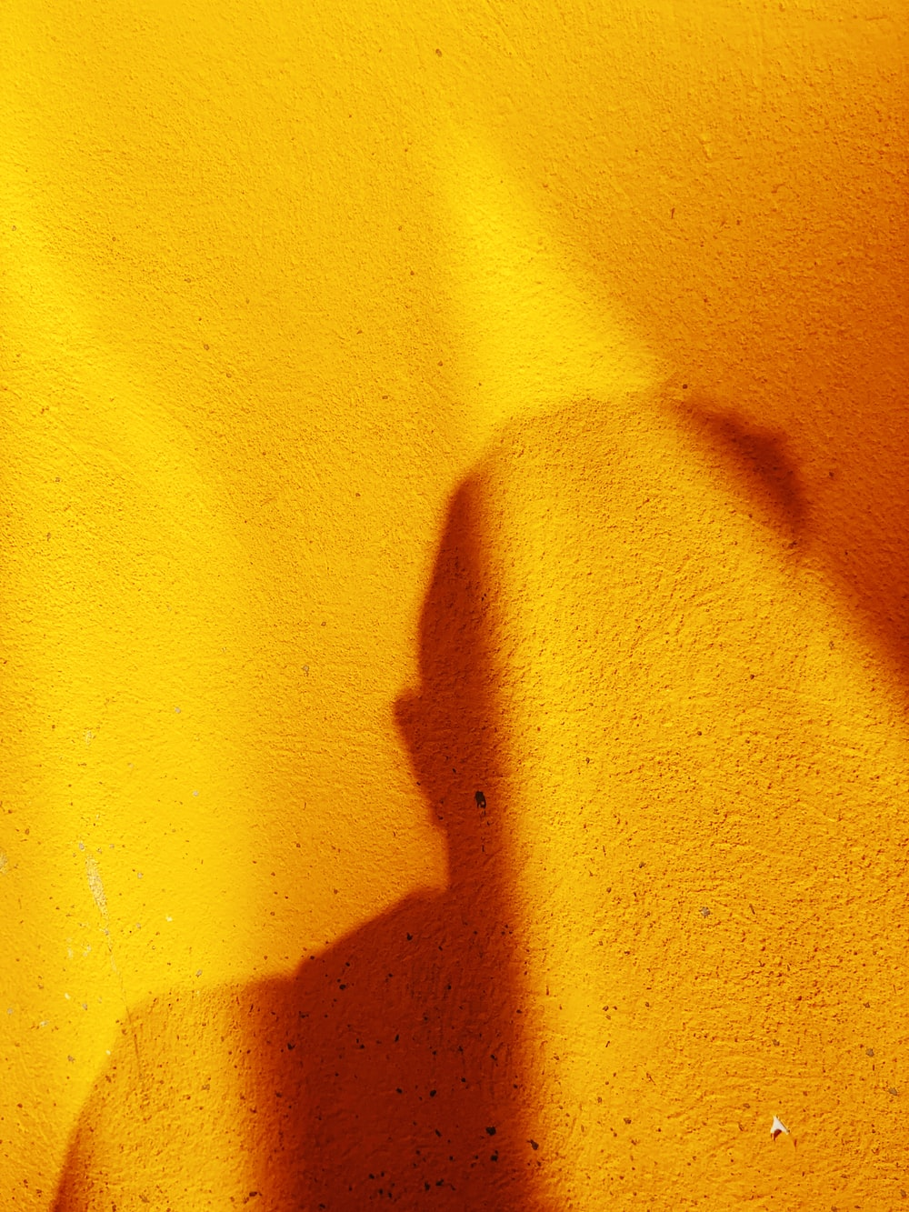 shadow of person on yellow wall