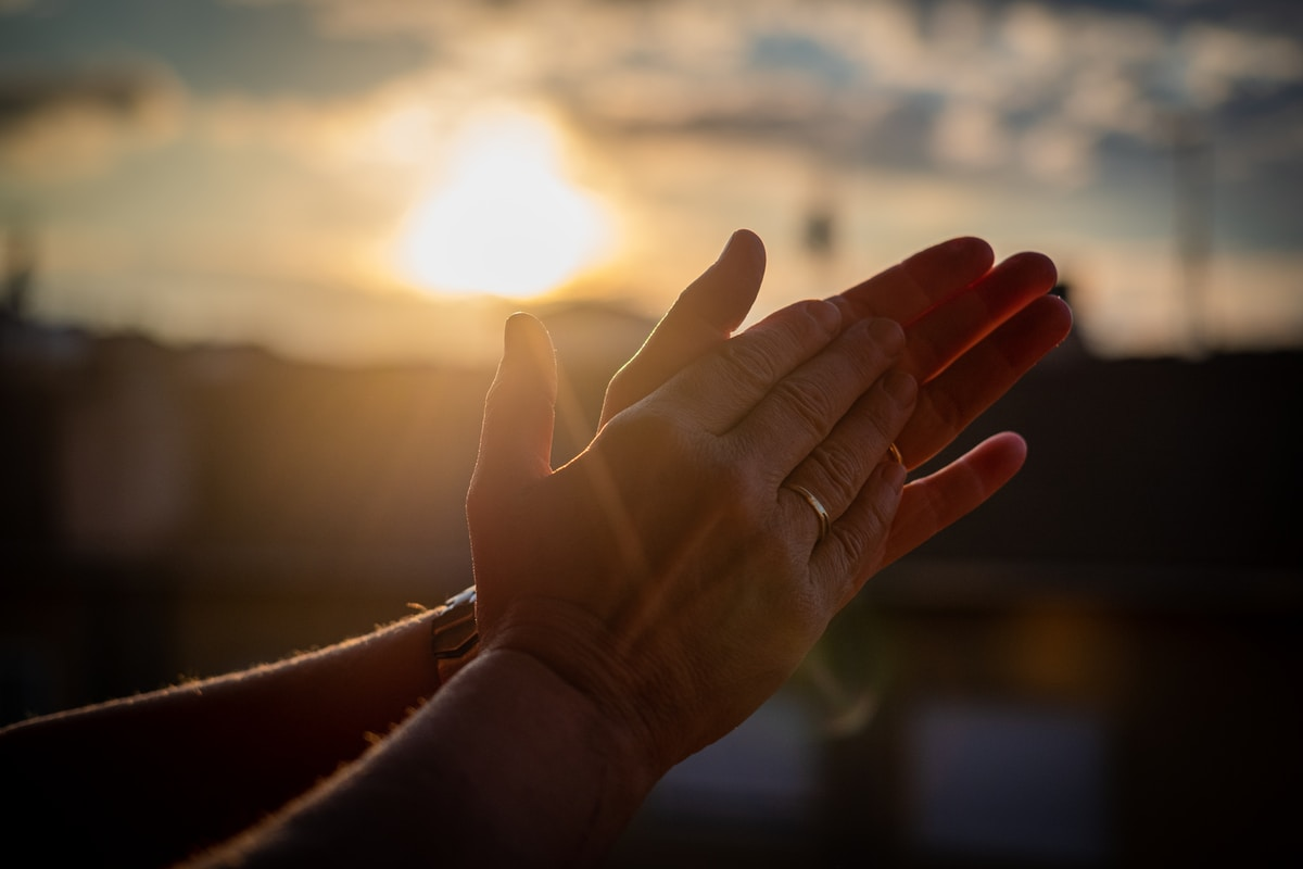A pair of hands clapping against a sunrise or sunset.