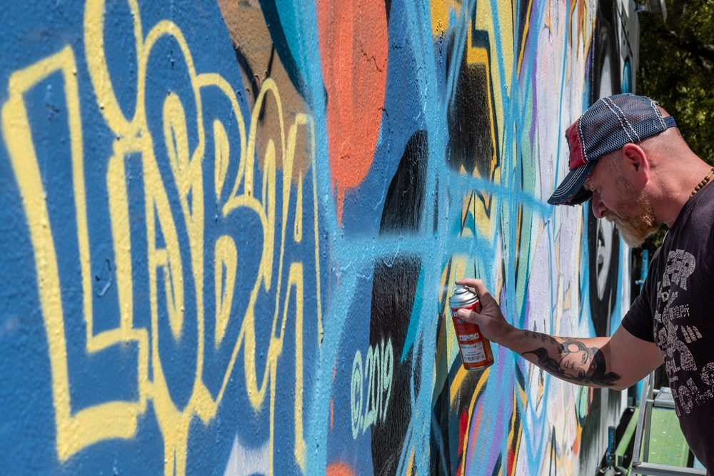 man in black t-shirt and blue denim jeans standing on graffiti wall