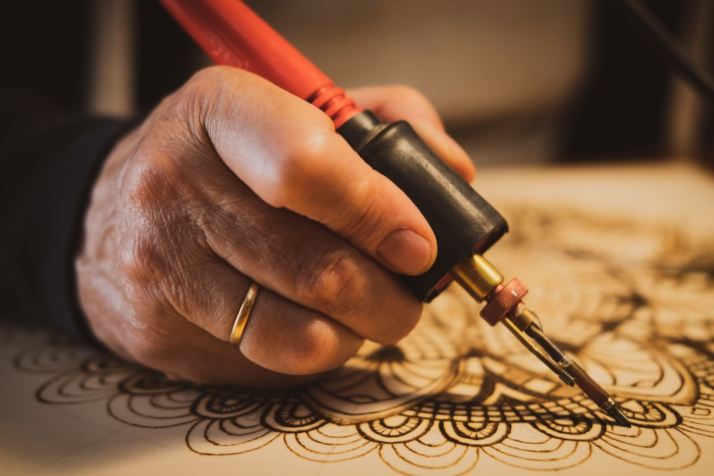 person holding red and black hand tool